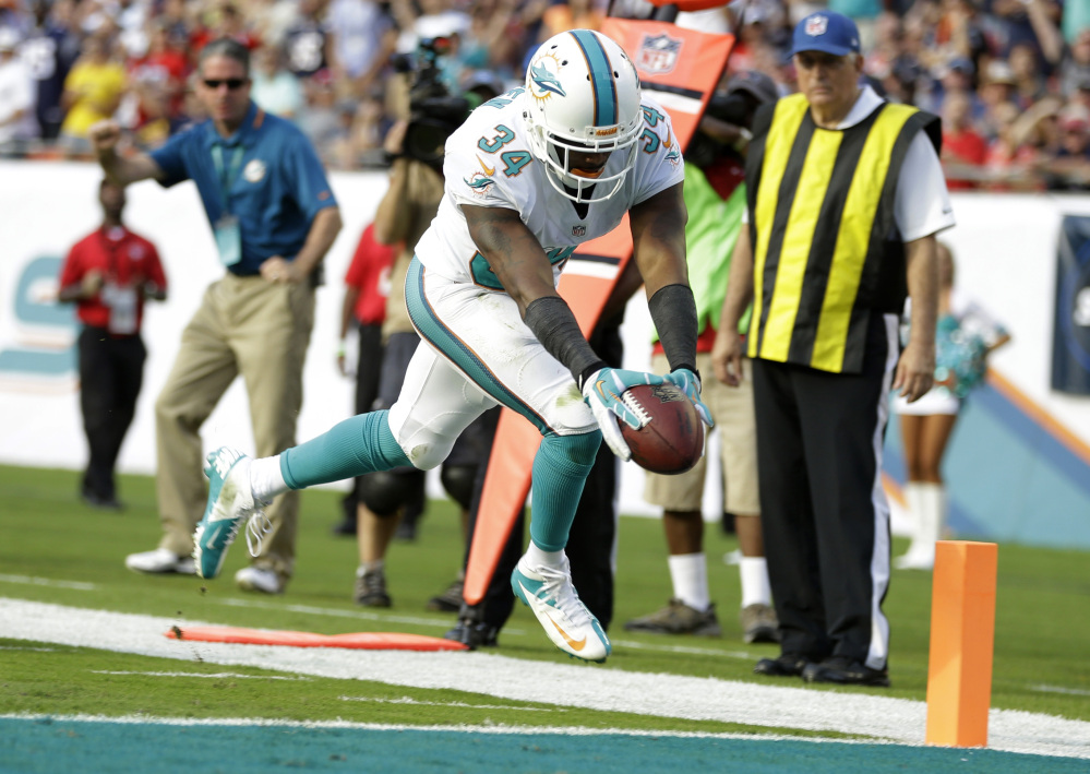Miami Dolphins running back Marcus Thigpen scores a touchdown during the second half against the New England Patriots on Sunday.