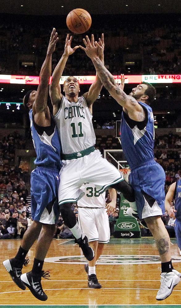 Boston Celtics' Courtney Lee (11) drives for the basket between Minnesota Timberwolves' Dante Cunningham, left, and Nikola Pekovic in the second quarter Monday.