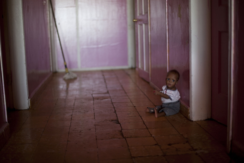 Ten-month-old Martelly Jean Louis sits alone on the floor of the U.S.-based Church of Bible Understanding orphanage in Kenscoff, Haiti. The orphanage is run by a Christian missionary group funded by the Olde Good Things antique store on Manhattanís Upper West Side.