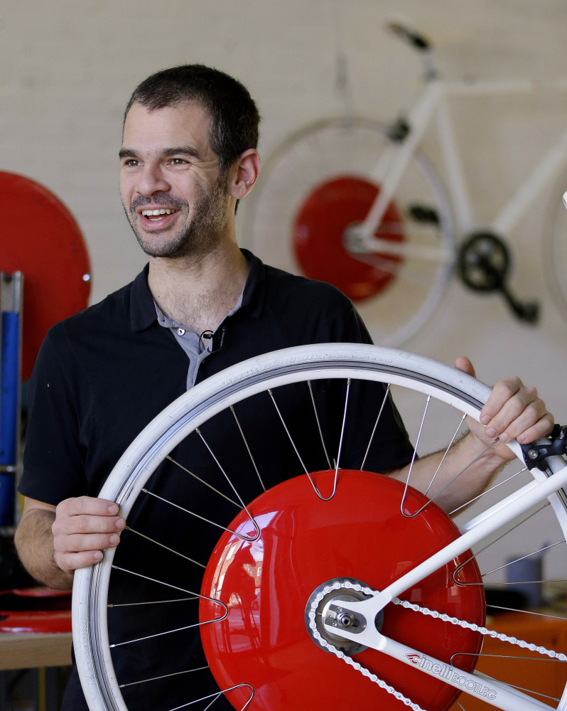 Assaf Biderman, co-inventor of the Copenhagen Wheel, poses with his invention at Superpedestrian in Cambridge, Mass.