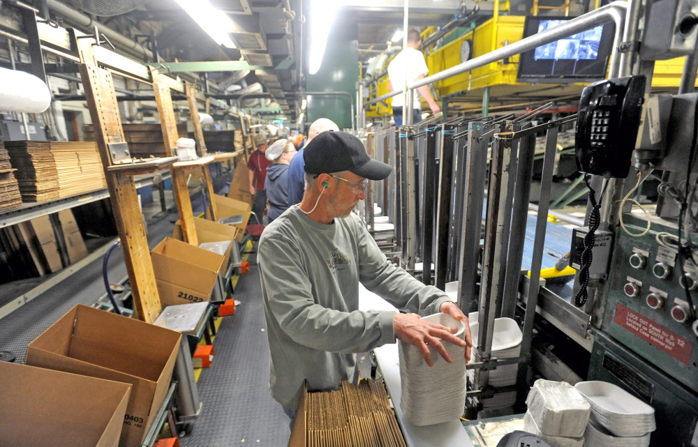 Mike Hamel stacks paper products during his shift at Huhtamaki in Waterville on Wednesday.