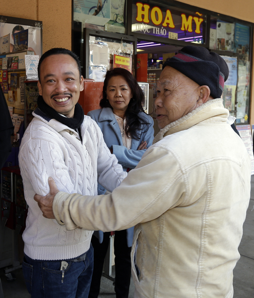 Jenny's Gift Shop owner Thuy Nguyen, left, is congratulated by a customer Wednesday in San Jose, Calif., after his shop sold one of two lucky winning tickets in Tuesday's near-record $636 million Mega Millions drawing. He'll get $1 million for selling the winning ticket. The other was sold at a tiny newsstand in Atlanta.