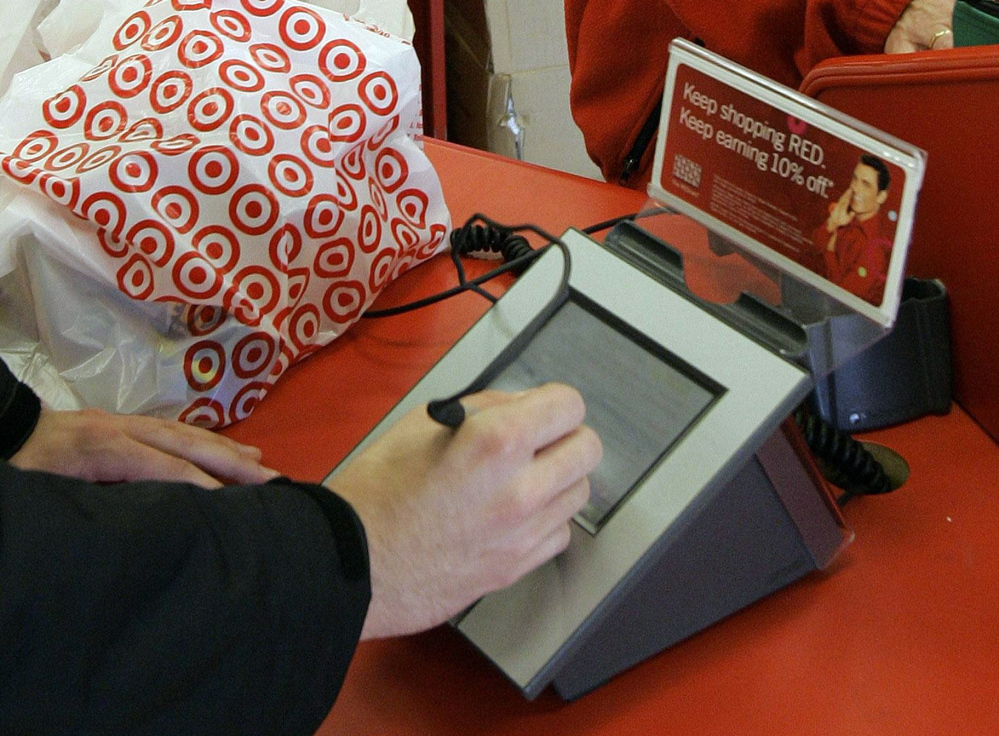 A customer signs after using his credit card. The data stolen recently included each user's name, card number, expiration date and three-digit code.