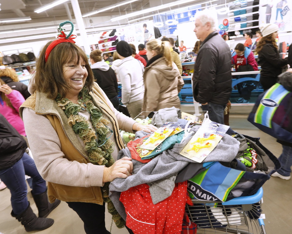 Barbara Adjutant of Biddeford rolls her cart through a long line at Old Navy in South Portland shortly after midnight Friday, Nov. 29. Nationwide stores are planning a sales blitz to finish the holiday shopping season, including round-the-clock hours.