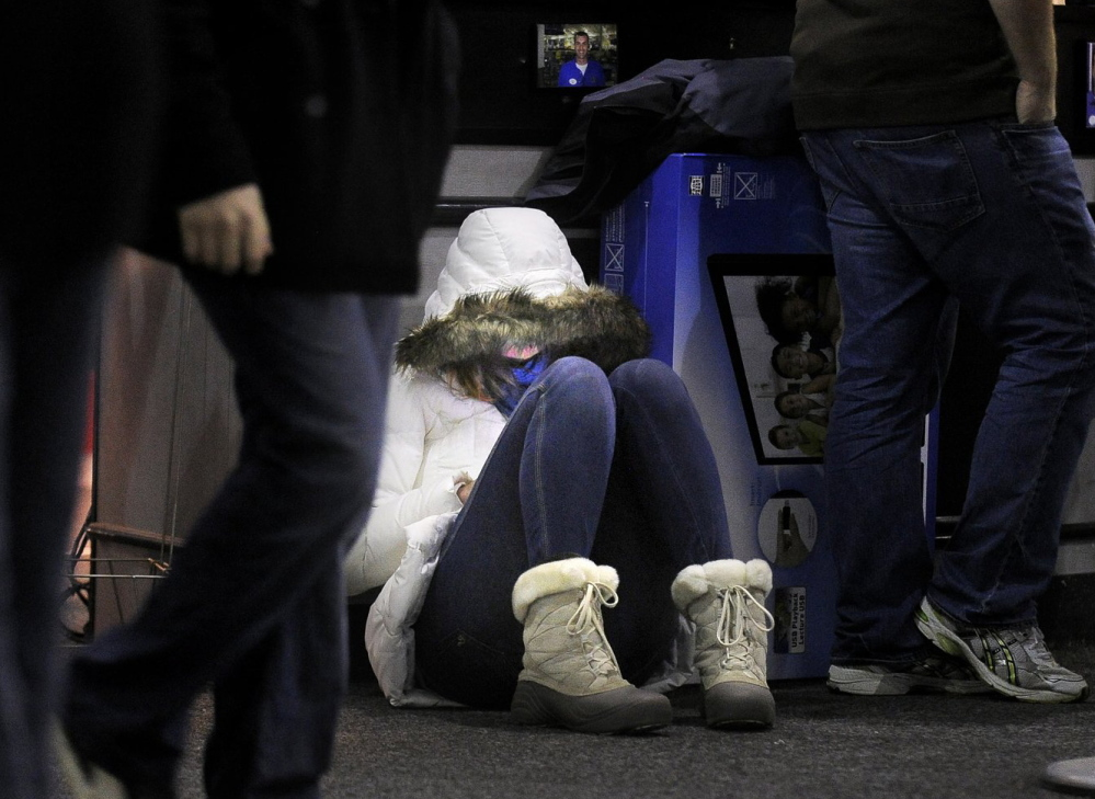 Amy Barham of South Portland sits on the floor of Best Buy early Nov. 23, 2012, while waiting for others to finish shopping.
