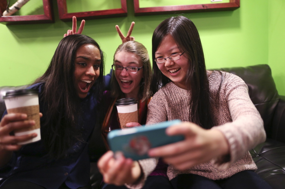 """Amrita Mohanty, 16, from left, Marta Williams, 16, and Michelle Mao, 15, take a Snapchat """"selfie"""" while having coffee Dec. 12 at the Steepery Tea Bar in Woodbury, Minn. The ubiquitous smartphone is causing a decline in sales of digital cameras."""