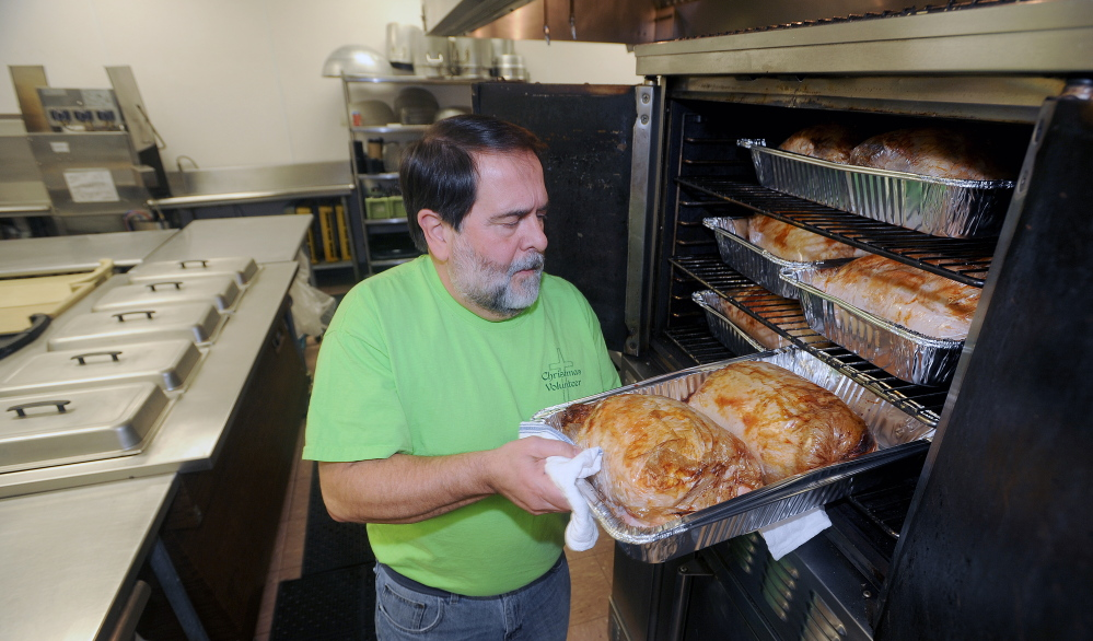 Richard Dionne, kitchen supervisor for the Central Maine Family Christmas Dinner, tends to turkey in the oven at the Elks Lodge in Waterville on Monday. This will be the seventh consecutive year that volunteers have offered a free dinner open to all on Christmas Day.
