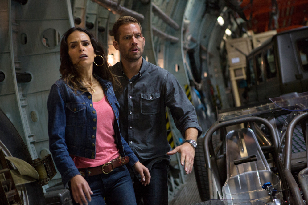 """This publicity image shows Jordana Brewster, left, and Paul Walker in a scene from """"Fast & Furious 6."""" Shooting on """"Fast & Furious 7"""" was about midway through when the 40-year-old Walker died in a car crash outside of Los Angeles."""