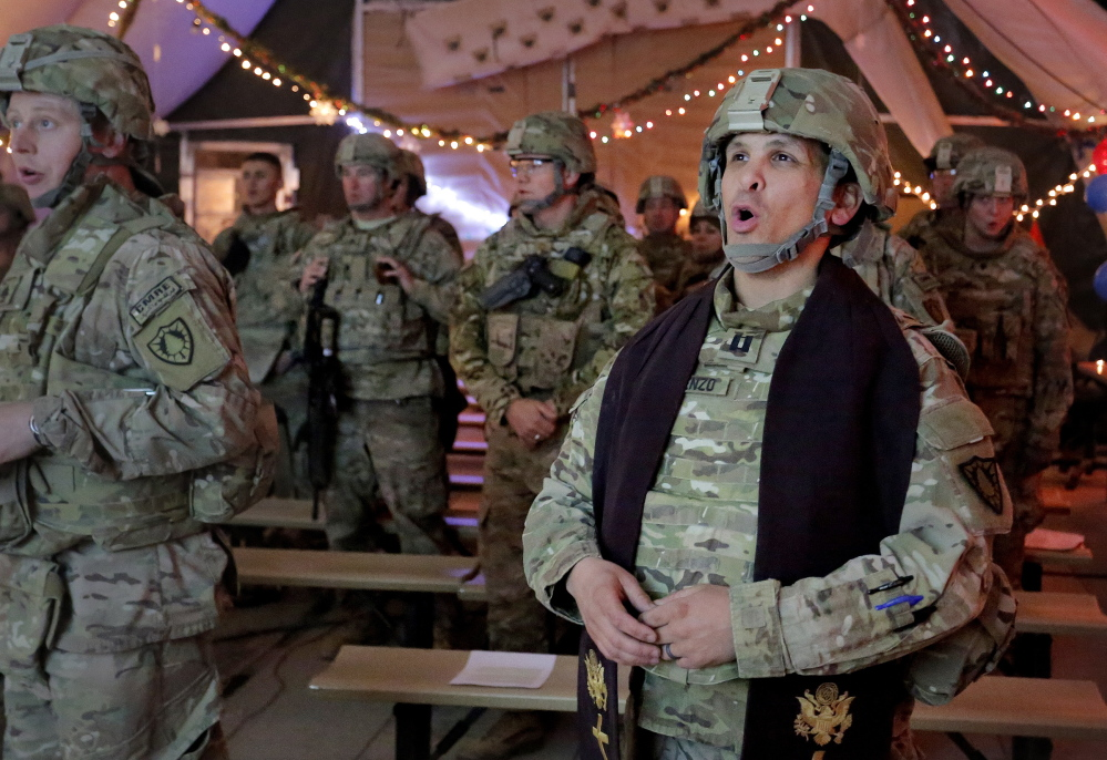 Capt. David DeRienzo, chaplain for the 133rd Engineer Battalion of the Maine Army National Guard, leads his congregation in prayer during a Christmas Eve service at battalion headquarters at Bagram Air Field in Afghanistan on Tuesday.