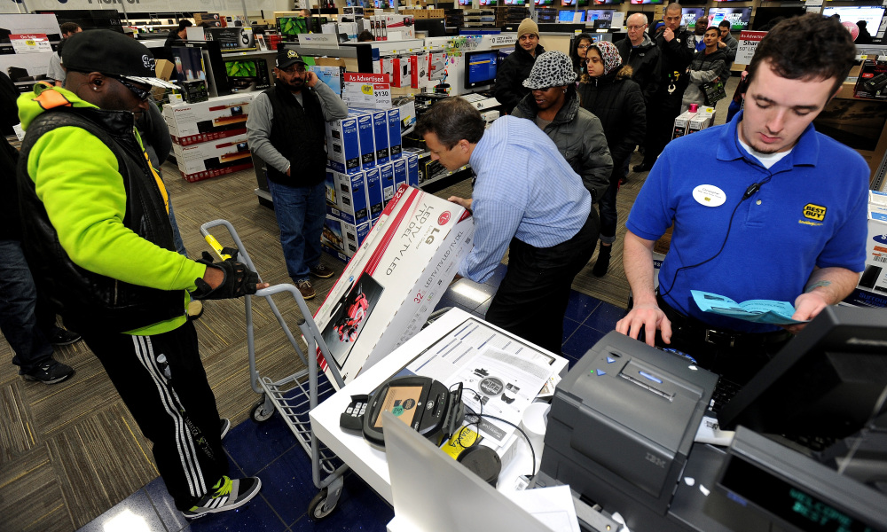 Best Buy employee Christopher Gervais, right, rings up a 32-inch LED TV in Dunwoody, Ga.
