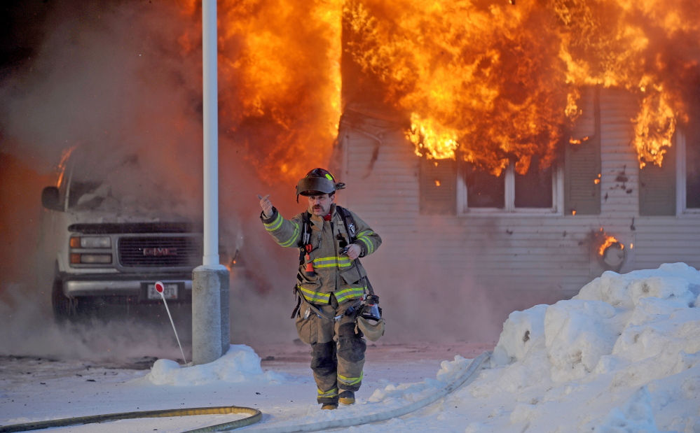 A Waterville firefighter gestures to other first responders on Christmas Day as they arrive to battle a fire that destroyed a garage used for storing flooring supplies.