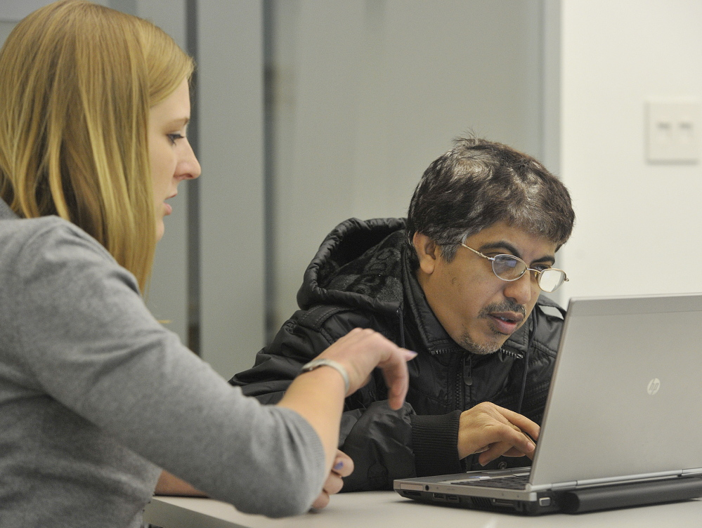 Libby Cummings, an outreach and enrollment specialist for the Portland Community Health Center, helps recent immigrant Tarunkumar Vaswani file his insurance request at the Portland Public Library on Friday.