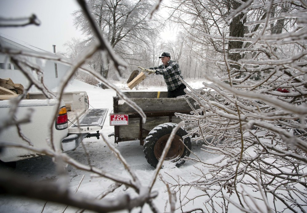 Ice from Monday's storm still clings to branches as Ken Finnegan loads his truck with firewood Thursday in Litchfield. With electricity out, some Maine residents seek alternative ways to heat their homes.