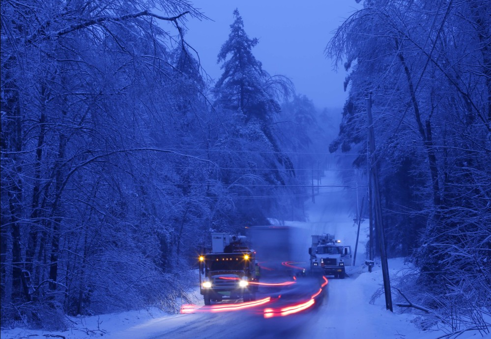 Traffic moves past utility crews as they prepare to work on power lines on Thursday in Litchfield, where many have been without electricity since Monday's ice storm. A storm on Sunday may throw more wrenches into repair efforts.