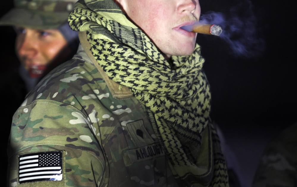 Spc. Carl Ahlquist of Scarborough enjoys a cigar before setting out from Bagram Air Field with the Convoy Escort Team on Dec. 20.