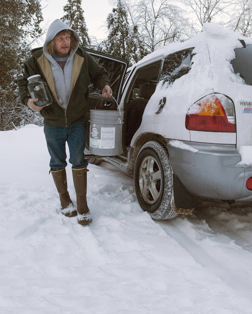 Dexter Smith carries water for drinking and other uses Monday into his home on Settlers Landing Road in Hancock. At the peak, 120,000 were without power after the ice storm in Maine a week ago.