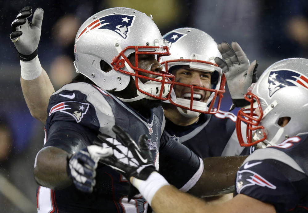 New England Patriots running back LeGarrette Blount, left, celebrates his touchdown against the Buffalo Bills with Danny Amendola, center, and James Develin, right, in the fourth quarter Sunday in Foxborough, Mass.
