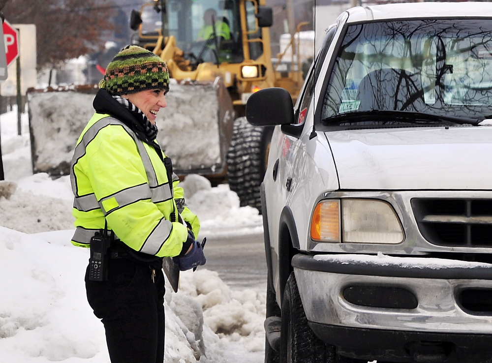 """Dressed for the cold weather, Ann Rand, parking control officer for Portland, coordinates the towing of a truck parked in a city services tow zone on North Street as crews atempt to remove snow from the last two storms. Her comment: """"It's cold!"""""""