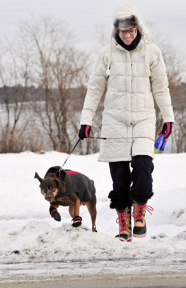 Dressed for the cold weather, Margaret Ybarra walks her dog Hunter, who is dressed in warm boots, along the Eastern Prom in Portland on Tuesday.