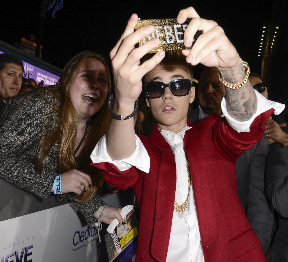 "Singer Justin Bieber takes a ""selfie"" with a fan at the premiere of the feature film ""Justin Bieber's Believe"" at Regal Cinemas L.A. Live in Los Angeles. The word selfie is on a list of among those words selected for elimination in Michigan's Lake Superior State University's 39th annual batch of words to banish due to overuse, overreliance and overall fatigue."