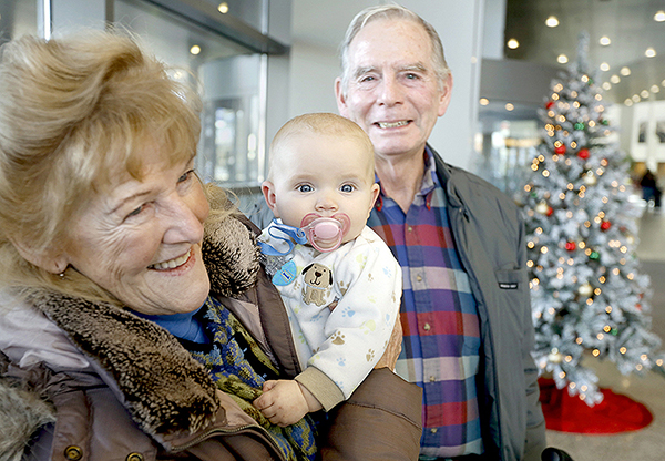 Manny Morgan of Cape Elizabeth holds her 7-month-old granddaughter Corinne Corbett at the Portland International Jetport while she and her husband, Chris Corbett, talk about the FCC moving to allow cellphone use during flights.