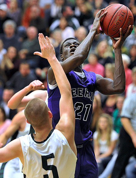 Ahmed Ismail Ahmed of Deering goes up with a shot over Bonny Eagle's Nick Dubay during Friday night's game in Standish. Bonny Eagle won the season opener, 67-58.