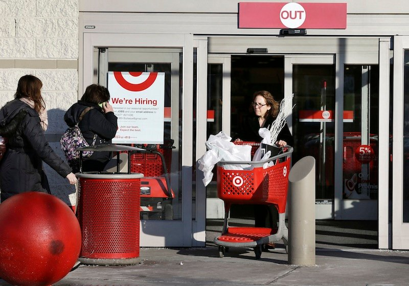 A woman pushes a shopping cart, right, while departing a Target retail store Thursday, Dec. 19, 2013 in Watertown, Mass. The nation's second-largest discount retailer said Tuesday that an unidentified number of gift cards sold over the holidays were not properly activated.
