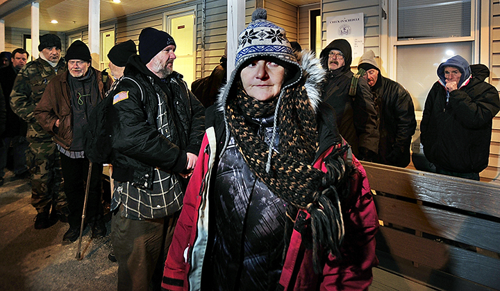 Laurel Merchant stands in line in the cold with dozens of others as they wait to get in to the Oxford Street Shelter for the night. Friday, December 13, 2013. Gordon Chibroski, Staff Photographer