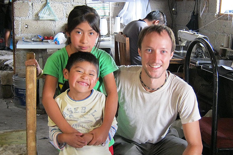 Levi Bridges poses with the children of a Mexican family he interviewed and stayed with during his fieldwork in Mexico to document the lives of migrant workers.