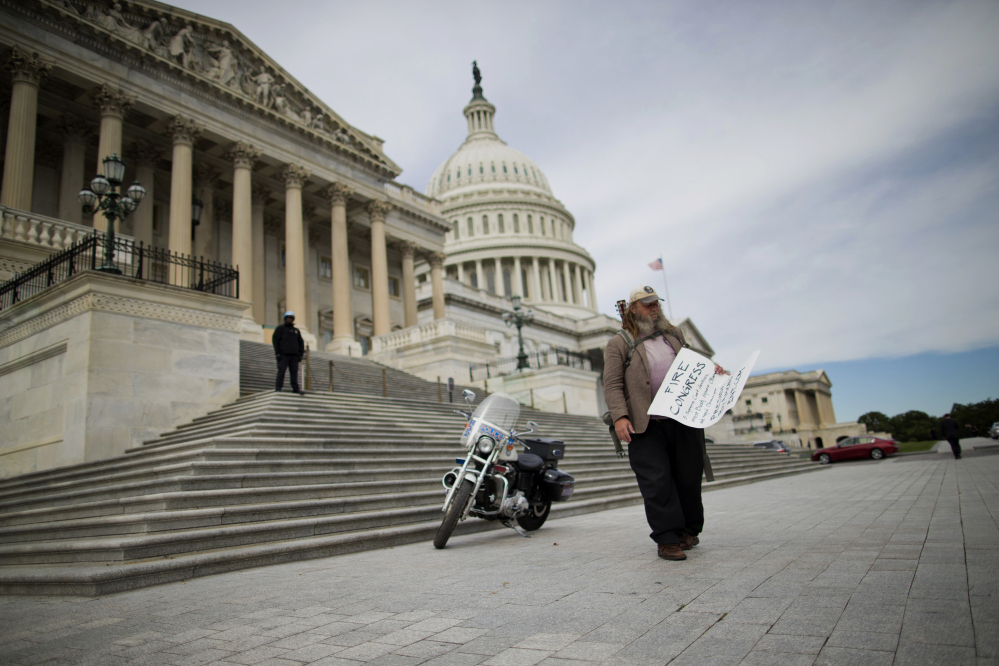 "Rick Hohensee of Washington carries a ""Fire Congress"" sign on Capitol Hill in October. Americans enter 2014 with a negative view of their government, expressing little hope that elected officials can or will solve the nation's problems."