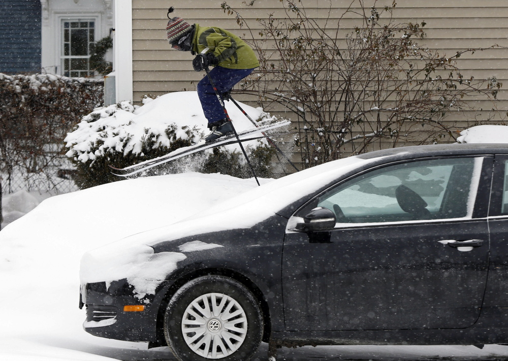 Milo Bloom, 10, skis over a snowbank next to a parked car during Thursday's snowstorm in Portland. Strong winds were creating blizzard-like conditions overnight.