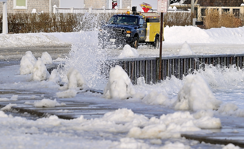 Eric Cloutier, an employee of the Kennebunk area water district, braves the waves splashing over the road as he heads for a water pipe break at one of the residences along the ocean. The road was closed to all but local traffic and workers.