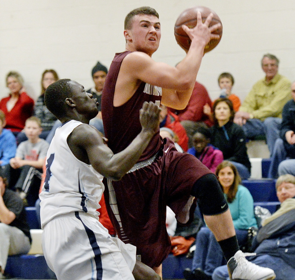 Spencer Hodge of Windham drives to the basket Friday night as Moses Abwoch of Westbrook defends Friday night during their SMAA boys' basketball game at Warren Gym. Westbrook took control early and rolled to a 60-46 victory.