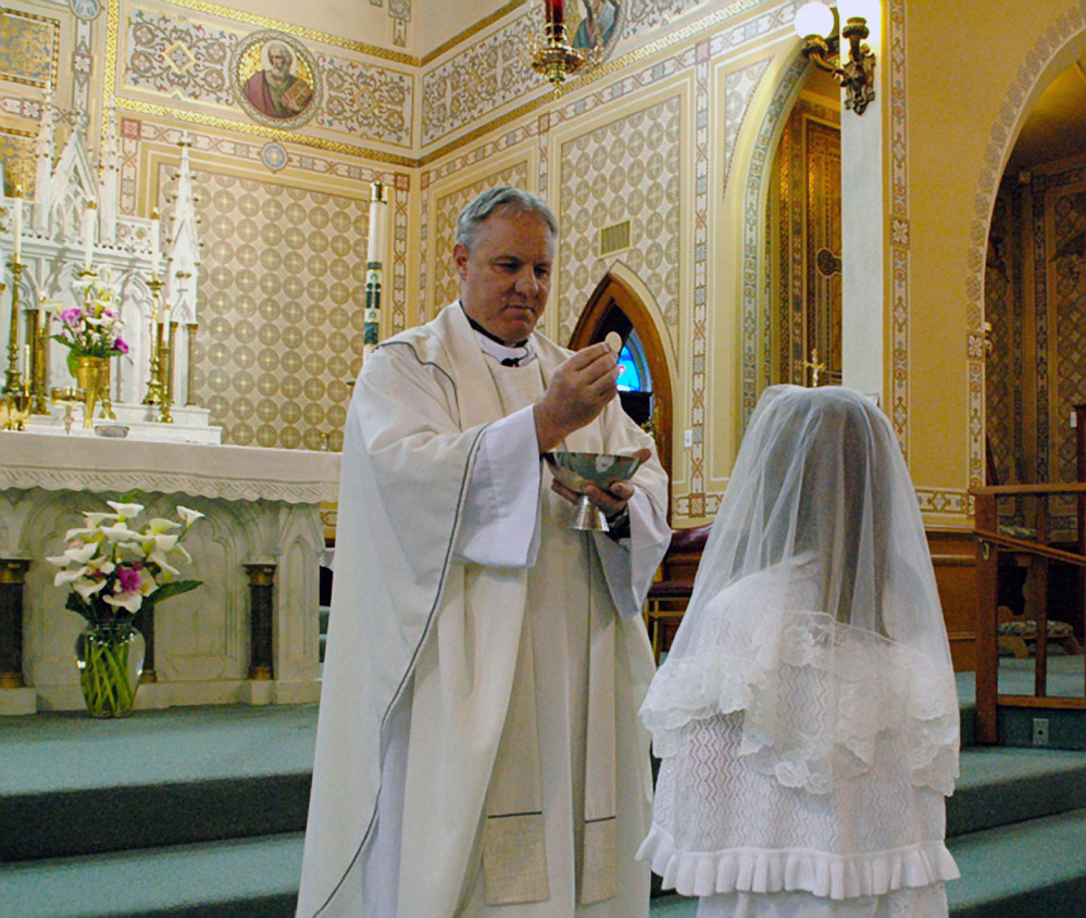 This May 2012 photo provided by Lynn Enemark shows the Rev. Eric Freed administering First Communion in St. Bernard Catholic Church in Eureka, Calif. Freed was found slain New Year's Day in the rectory of the church. A suspect has been arrested who police say was in jail the day before behaving erratically but was released after being evaluated at a hospital.