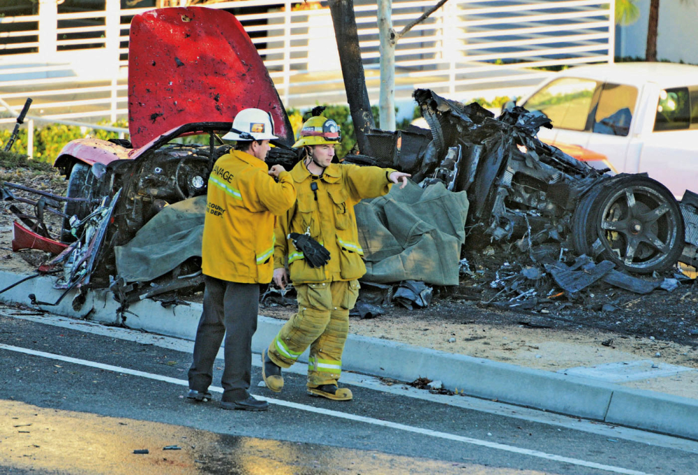 In this Nov. 30, 2013, photo, sheriff's deputies work near the wreckage of a 2005 Porsche Carrera GT that crashed into a light pole in Valencia, Calif. The Los Angeles County coroner's office says that Roger Rodas, Paul Walker's friend and financial adviser, was driving the car at an unsafe speed.