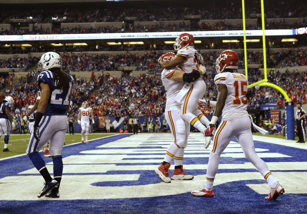 After scoring a 10-yard touchdown reception, Kansas City Chiefs running back Knile Davis (34) jumps into the arms of Geoff Schwartz (74) as wide receiver A.J. Jenkins (15) moves in during the second half of an NFL wild-card playoff game Saturday in Indianapolis. Colts defensive back Josh Gordy (27) walks away.