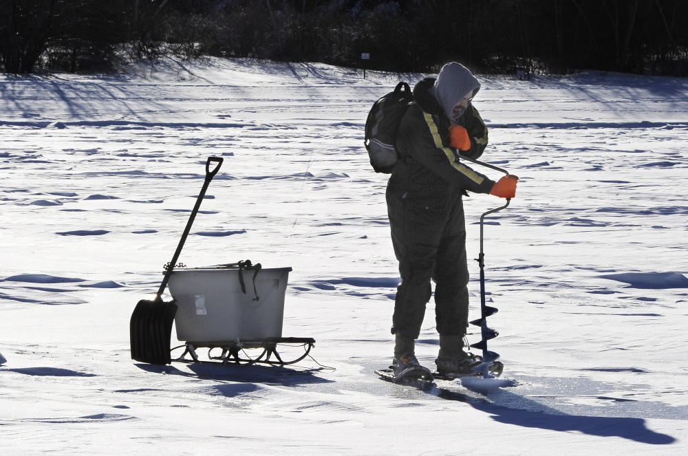 Walter Selens of Gorham uses a hand auger Saturday to cut a hole for fishing on Sebago Lake's Lower Bay in Standish.