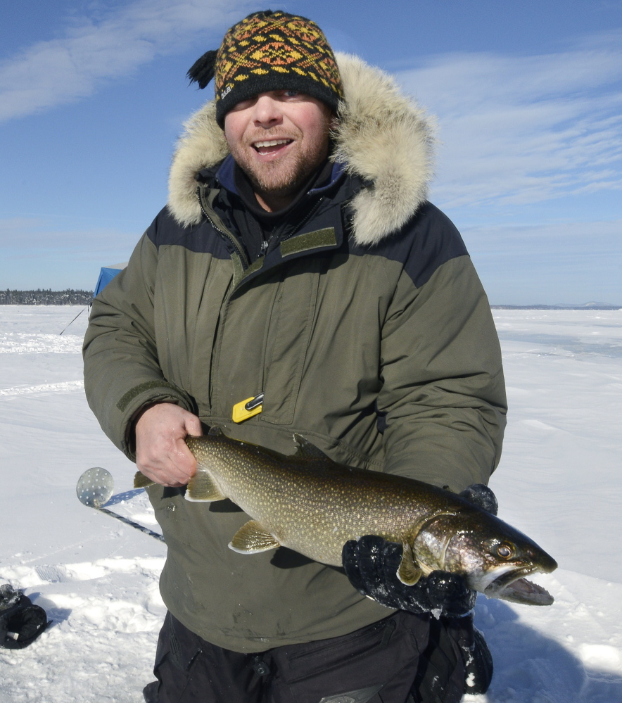 Mike Lorello of South Portland shows a togue, or lake trout, that he caught and then released Saturday during an ice-fishing outing on Sebago Lake.