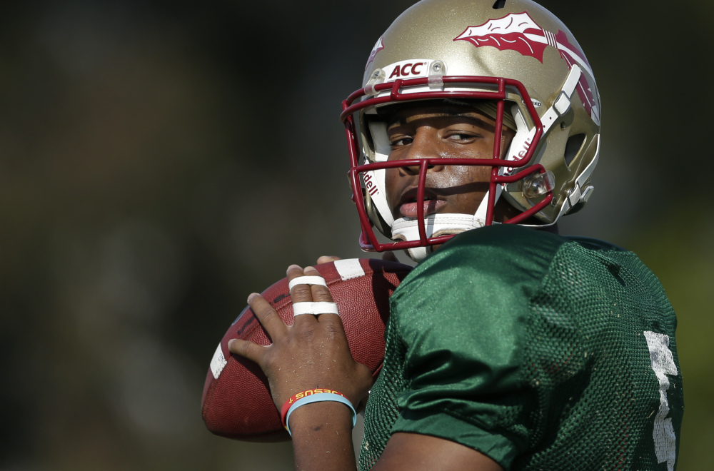 Florida State quarterback Jameis Winston looks to pass during the Seminoles' practice on Friday. Winston set freshman records in leading Florida State to a 13-0 record.