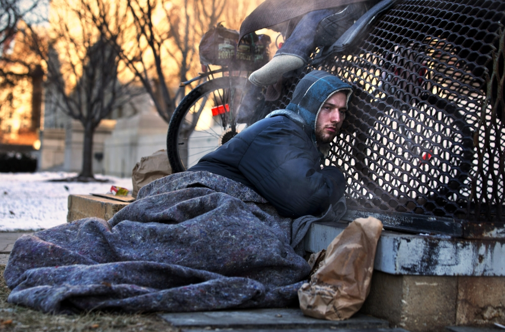 Nicholas Simmons, 20, of Greece, N.Y., warms himself on a steam grate with three homeless men by the Federal Trade Commission, just blocks from the Capitol, during frigid temperatures in Washington, on Saturday.