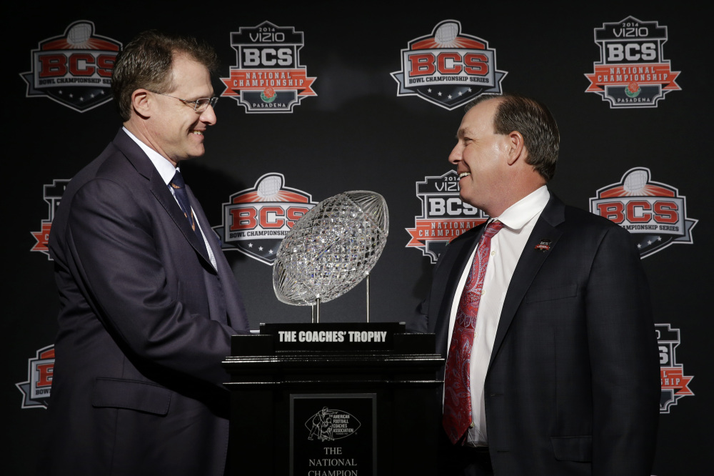 Auburn Coach Gus Malzahn, left, and Florida State Coach Jimbo Fisher shake hands Sunday in front of The Coaches' Trophy during a news conference for Monday's BCS championship game .
