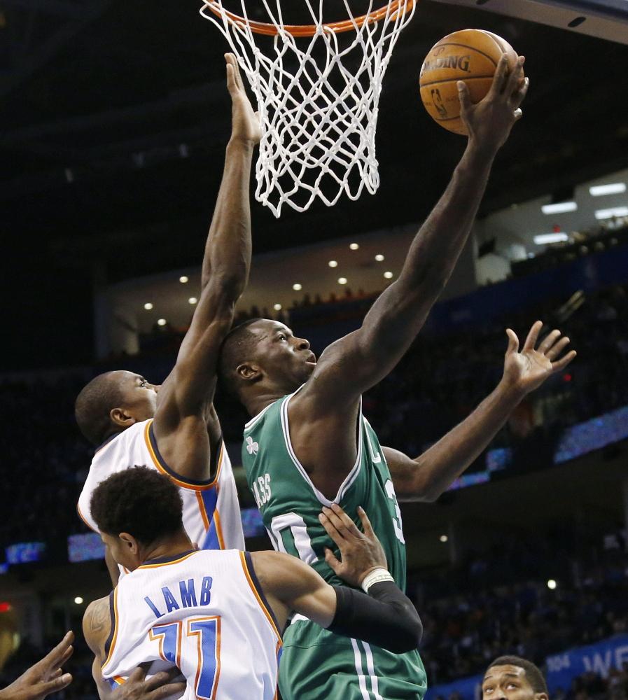 Celtics forward Brandon Bass puts up a shot against Oklahoma City's Serge Ibaka and Jeremy Lamb during Boston's 119-96 loss Sunday night.