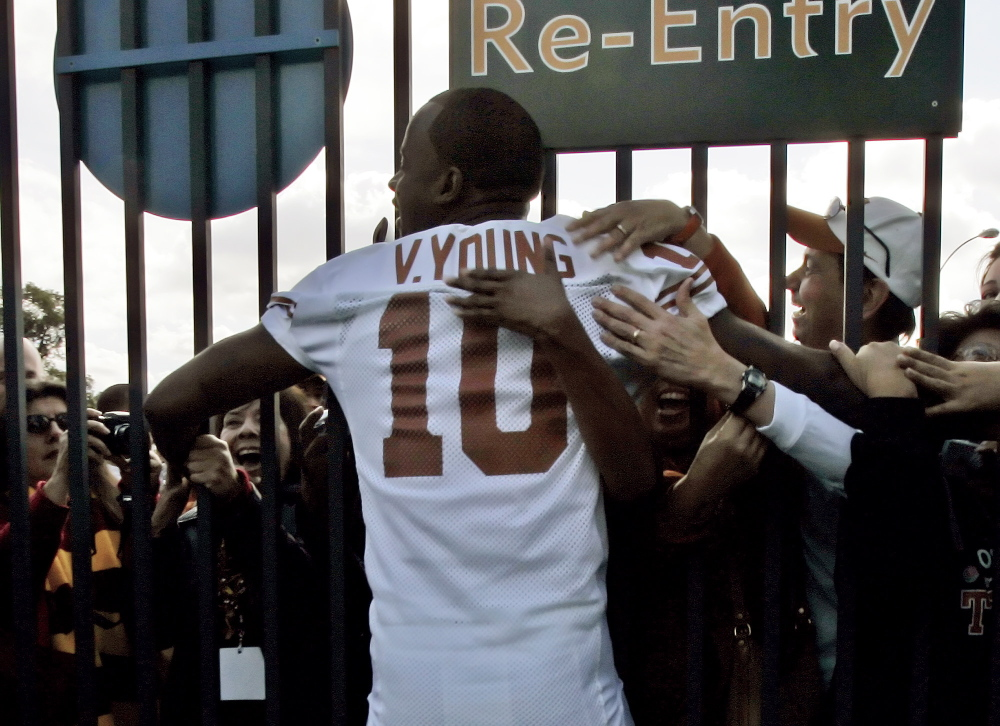 University of Texas quarterback Vince Young is hugged by fans at the gate of the Rose Bowl in Pasadena, Calif., on Jan. 3, 2006.