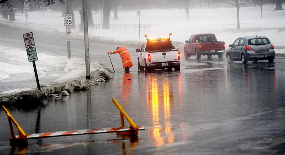 Jim Sloan, who works for the city of Portland, clears a storm drain on State Street where the street had flooded Monday. A road barrier had been set up to keep vehicles away from the water but the wind had blown it over.
