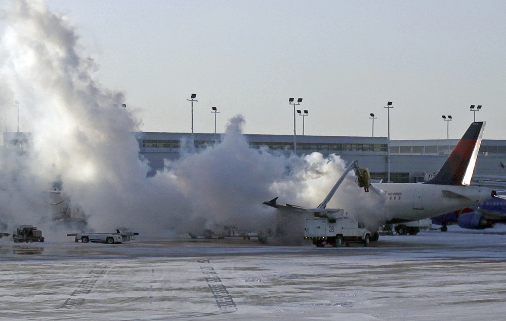 A Delta plane is deiced at Chicago Midway International Airport Monday, Jan. 6, 2014, in Chicago. The bitter weather comes after a heavy snowstorm hit much of the region last week. More than 400 flights were cancelled at Chicago's airports Monday.