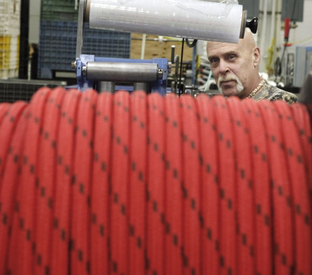 Mike Fowler coils double-braided rope at Yale Cordage in Saco on Thursday. The company is developing ultrastrong rope to securely tether buoys to warn of tsunamis and severe weather.