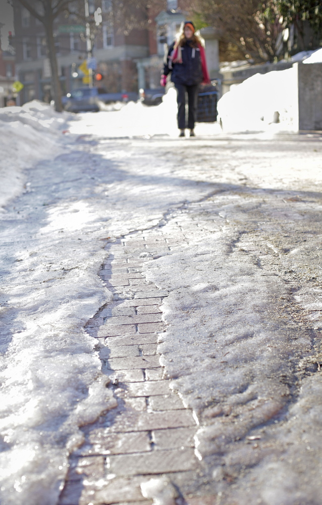 Morning temperatures around 14 degrees freeze the ice on sidewalks along State Street, making walking difficult in Portland on Tuesday.
