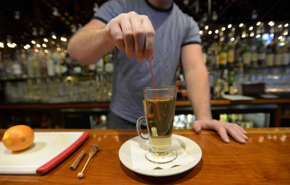 Patrick Morang, bar manager at David's in Portland, stirs a Hot Paddy that's made with spice-infused bourbon and orange bitters.