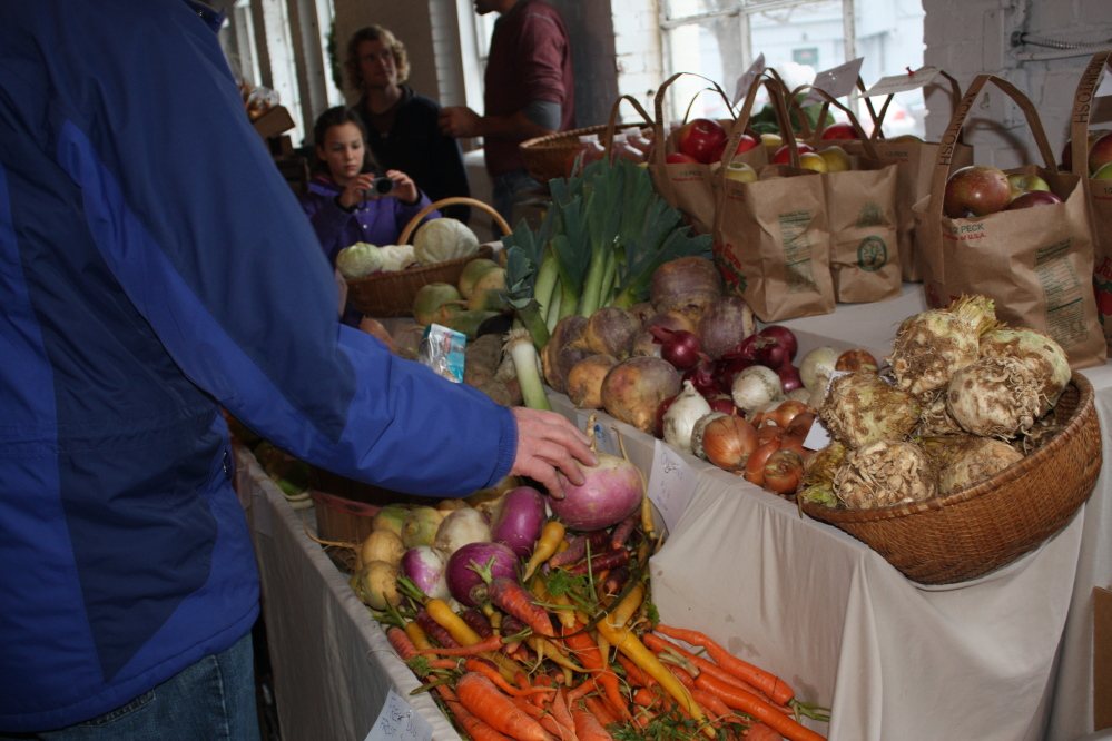 A customer selects a turnip at the Buckwheat Blossom Farm stand at the Portland winter market held in the Urban Farm Fermentory's food hub on Saturdays.