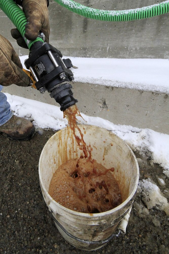 In a demonstration, a bucket is filled with beet juice at the Pennsylvania Department of Transportation's Butler, Pa., maintenance facility, on Monday, Because rock salt is largely ineffective below 16 degrees, road salt is mixed with additives, such as beet juice and cheese brine, to keep it working in temperatures as low as minus 25.